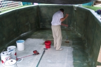This photo shows the process of applying fibreglass matting and vinyl ester  resin, to the walls and floor of pool.